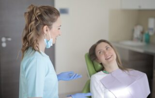 female dentist talking to patient